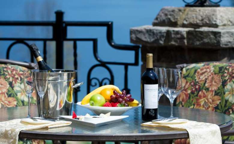 A round outdoor dining table, set on the porch of the Inn at Erlowest. You can see the water through the wrough-iron railing. The table is set with bottles of wine, glasses and a bowl of fruit.
