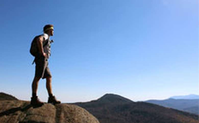 man standing on top of a mountain looking out at the distance