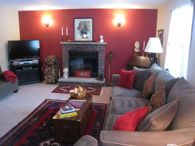 living room with a large couch, fireplace, tv, and red accent wall