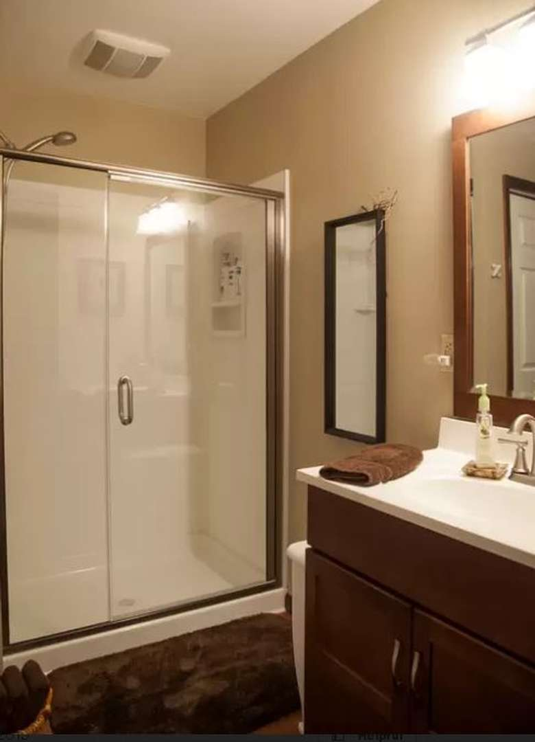 bathroom with a vanity and a large shower with glass door