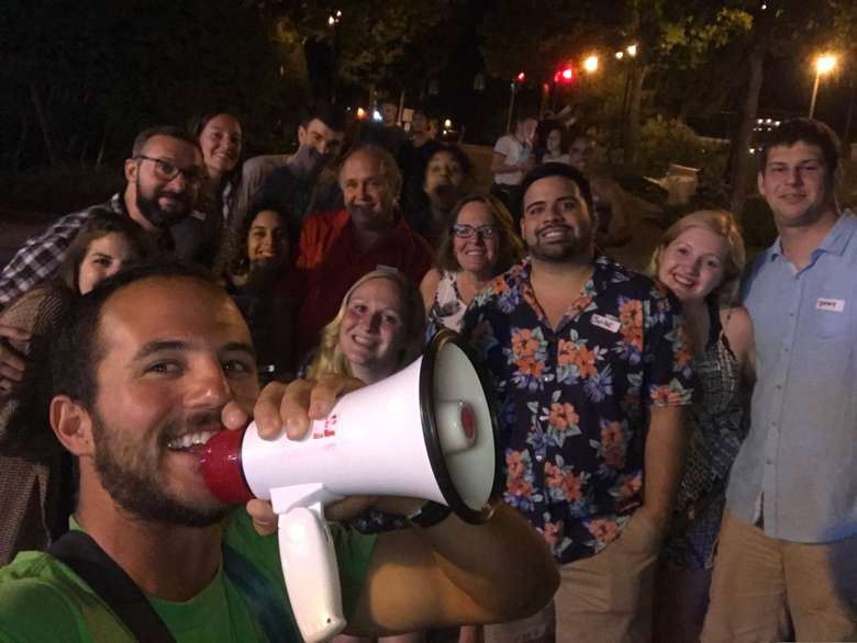 A selfie of a man holding a white megaphone with a group of smiling adults in the background