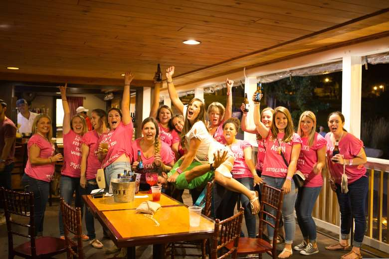 A group of women in pink t-shirts raising their arms and beers towards the camera. A women in white is in the middle and has jumped on the back of a man in a green t-shirt.