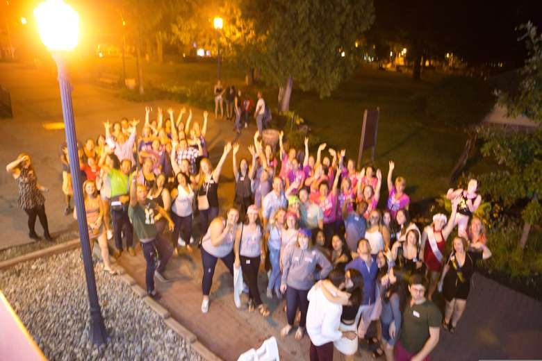 A shot from above a group of adults with their arms raised in the air. The photo is slightly out of focus.