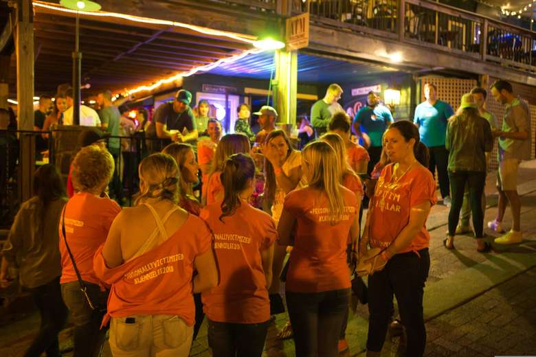 A group of women wearing pink t-shirts standing outside a bar. One woman is in white.