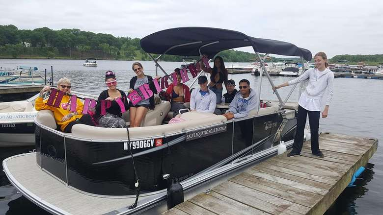 group of friends on a rental pontoon boat holding a happy birthday banner