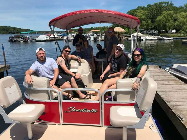 group of friends on a red rental pontoon boat
