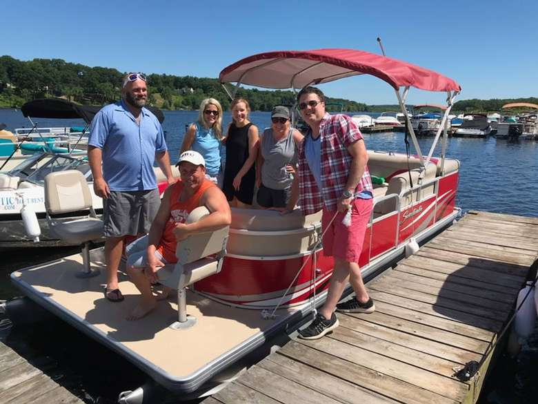 six people posing near the bow of a red rental pontoon boat
