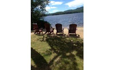 adirondack chairs lined up on beach overlooking long lake