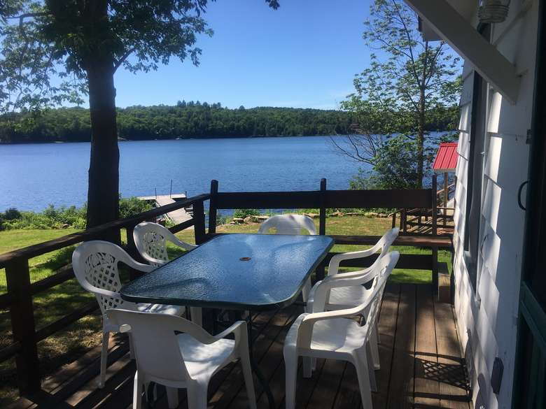outside deck of cabin number 8 with table and chairs overlooking long lake