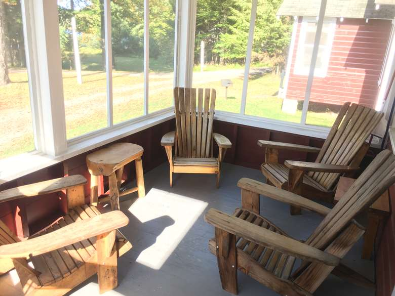 screened porch of cabin number 2 with adirondack chairs