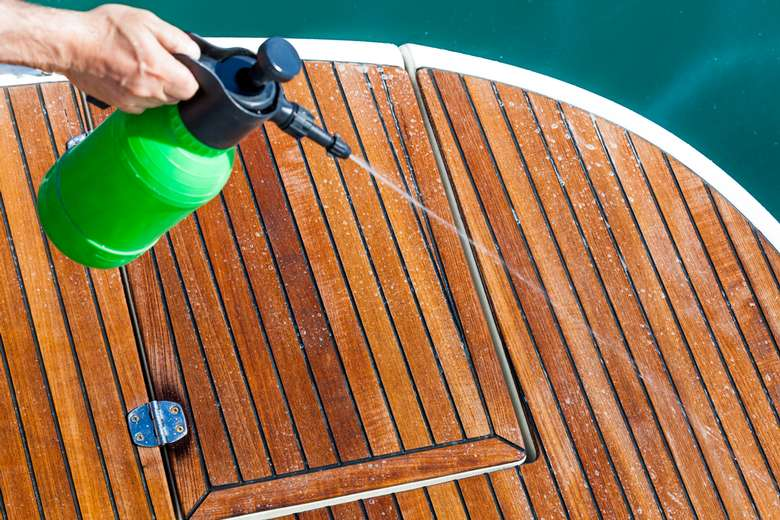 a hand holding a spray bottle and spraying liquid on to a boat deck