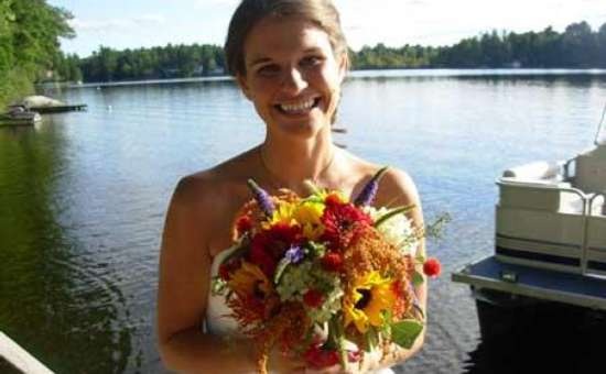 bride smiling and holding a colorful bouquet with a lake in the background