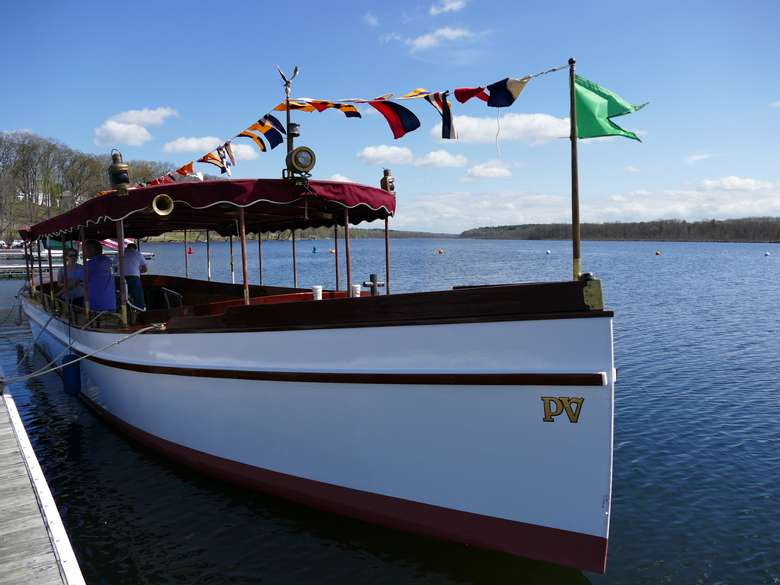 a Fantail Launch boat with flags along the top poles