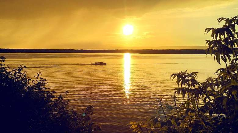a bright yellow sunset over a lake