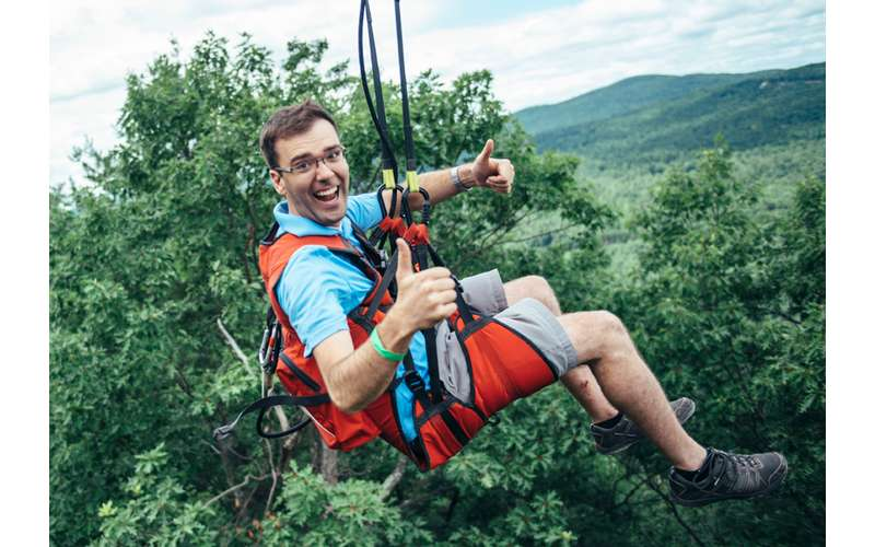 a guy ziplining while giving thumbs up
