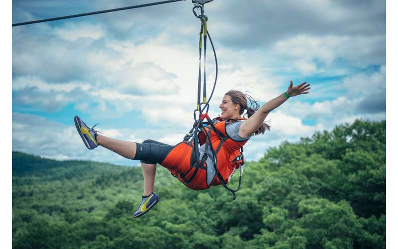 a woman ziplining with her arms out
