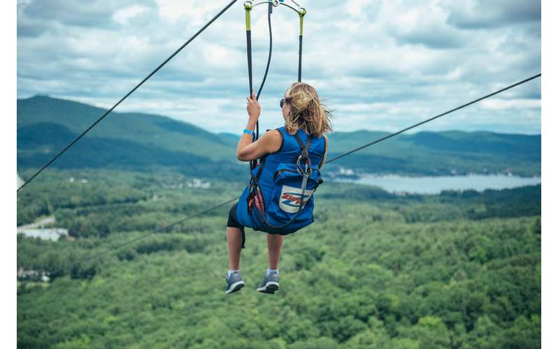 a woman ziplining with mountain views
