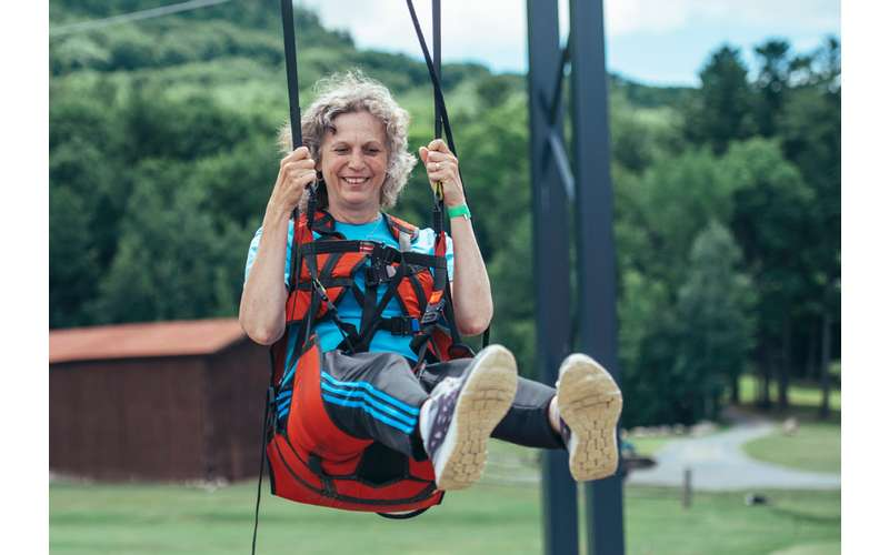 a woman ziplining and smiling