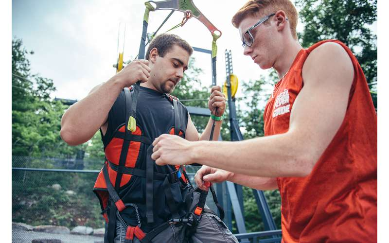 man helping another man into zipling gear