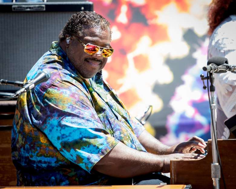 man plays piano, sunglasses on