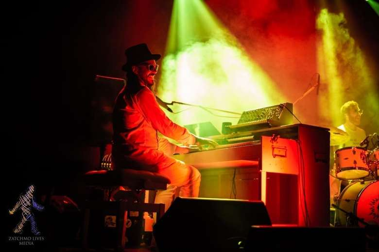man at piano on stage, it's smokey