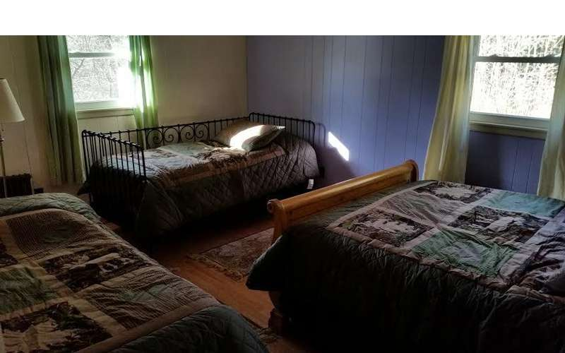 another view of bedroom with queen bed and two twin beds