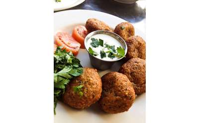falafel patties on a plate surrounding a small dish with a dipping sauce