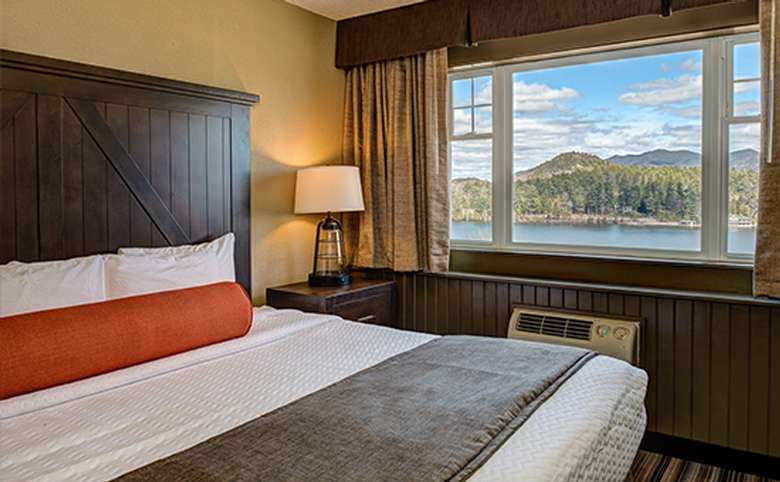 hotel room with a king-sized bed and a view of a lake out the window