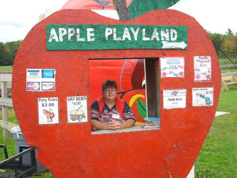 large apple sign that says apple playland with a worker ready to accept payment for activities
