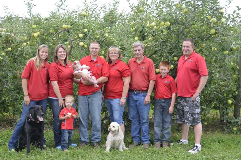 nine people in red shirts and two dogs posing for a picture in an apple orchard