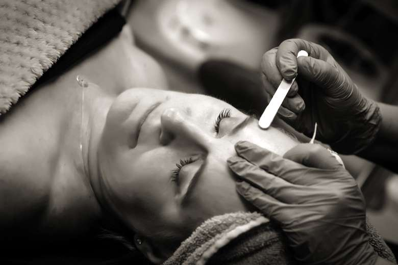 black and white photo of eyebrow waxing