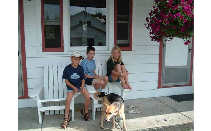 a family sitting outside a cottage