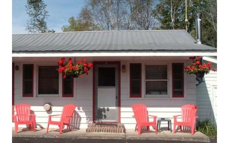 a cabin with pinkish Adirondack chairs in front of it