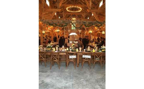 tables in a rustic barn set up for a wedding reception