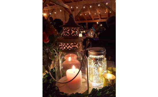 centerpiece with a candle in a lantern, a mason jar, and greenery