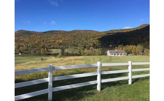 a white fence and a field on a sunny day in the fall