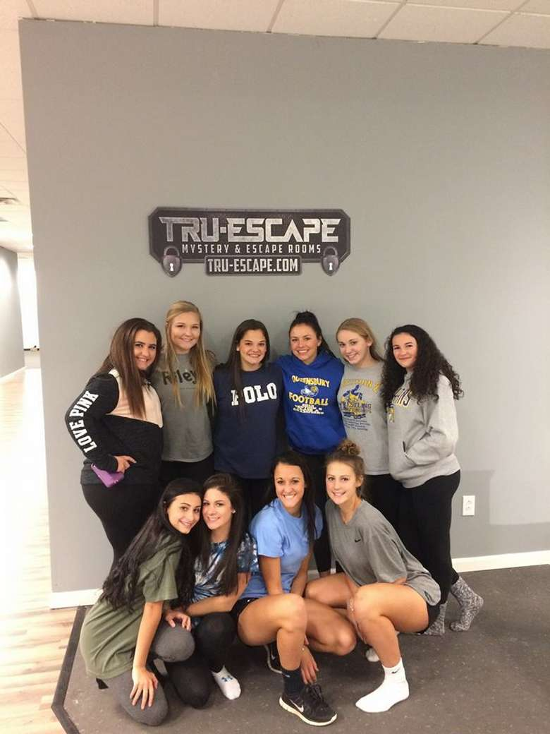 a large group of girls who are happy to have finished an escape room