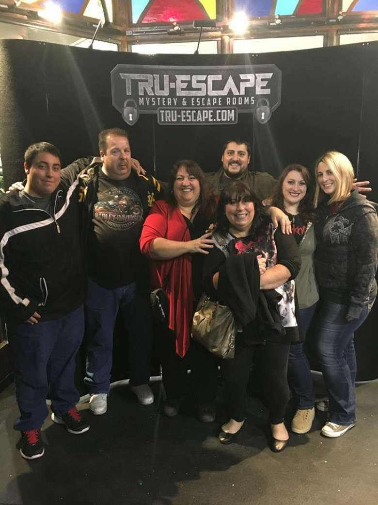 a fairly large group of women and men near an escape room sign