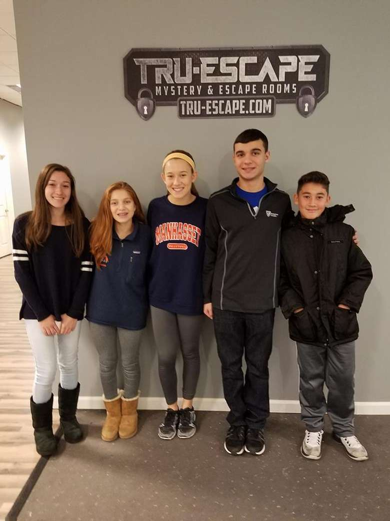 three girls and two boys standing under an escape room sign