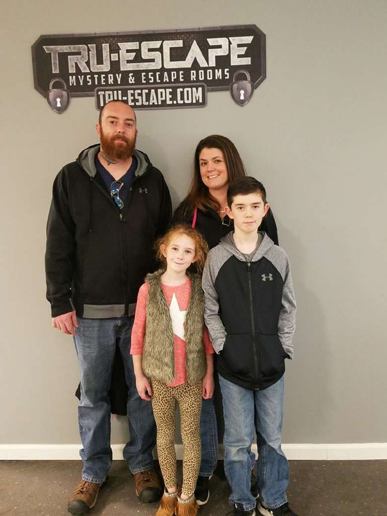 a family of four standing under a sign for an escape room