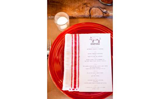 menu on top of a white and red napkin and red plate