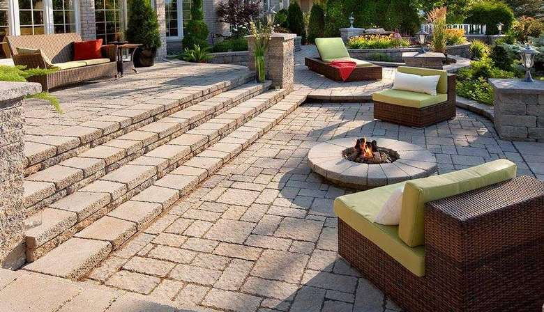 patio made from pavers with seating and a fireplace