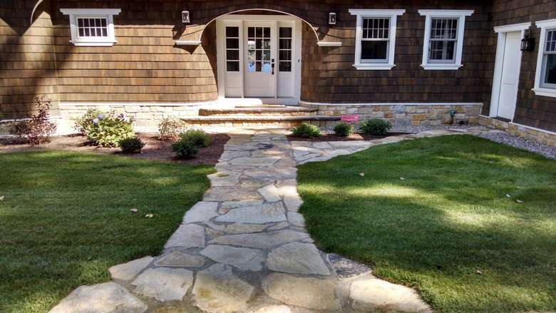 well-manicured lawn with a stone sidewalk leading to the front door