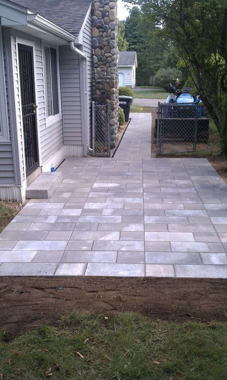 stone patio and walkway next to a house