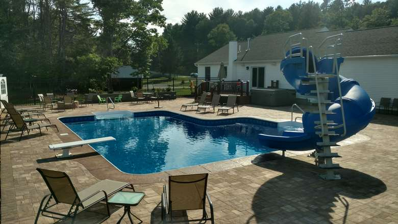pool area with a waterslide, diving board, and lounge chairs