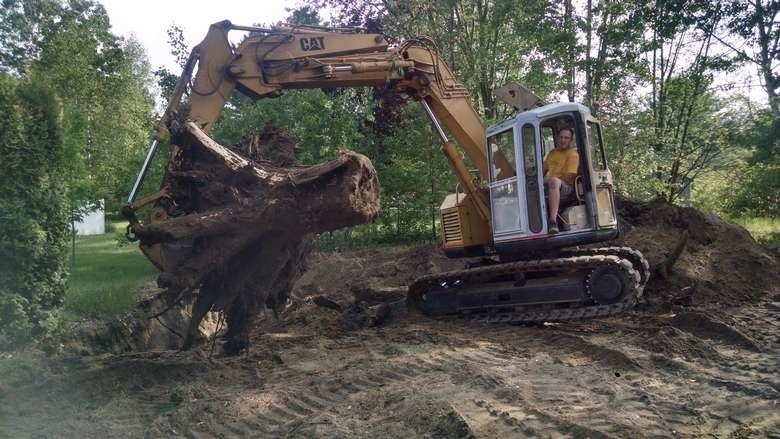 heavy machinery excavating a tree stump