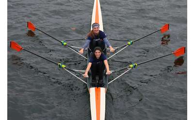 Two girls looking up at the camera smiling while rowing