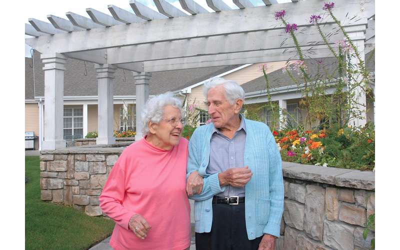 an elderly man and woman walking side by side outdoors near some flowers