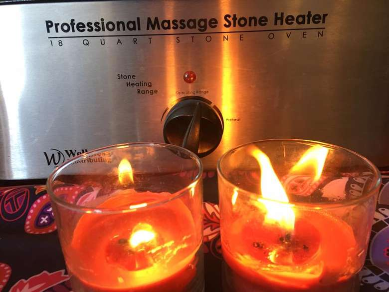 two candles in front of a massage stone heater