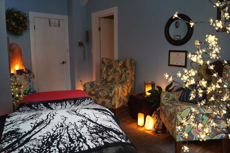 treatment room with low lighting, salt lamps, and a massage table